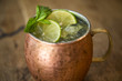 Close up of Moscow mule cocktail in a copper mug with lime slices and mint sprigs