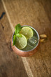 Top view of Moscow mule cocktail in a copper mug with lime slices and mint sprigs