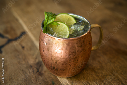 Moscow mule cocktail in a copper mug with lime slices and mint sprigs Poster