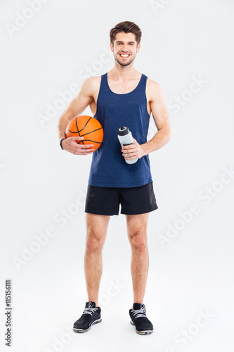 Smiling young sportsman holding basket ball and water bottle