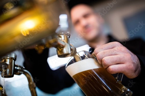Brewer filling beer in beer glass from beer pump Poster