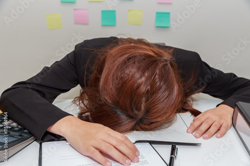 Poster Stressed businesswoman bend down the head at her desk, overwork