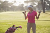 Confident mature woman carrying golf club