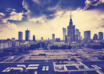 Old grainy film style Warsaw downtown with Palace of Culture and Science and skyscrapers at sunset, Poland.