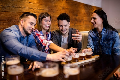 Friends enjoying beer at table Poster