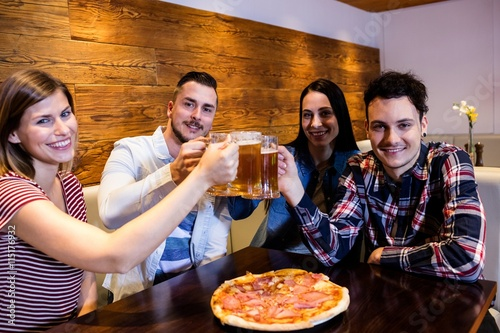Young friends smiling while toasting beer Canvas