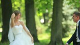 Pretty bride in elegant looking white dress and handsome groom have fun in park. Young woman pretend to slam her fiance with veil and he jokingly falls back
