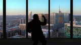 Happy business man celebrates in front of modern office window skyscrapers background