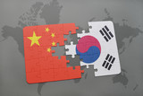 puzzle with the national flag of china and south korea on a world map background.