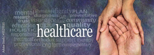 Health Care worker - female hands gently cradling male hands on a rustic dark stone background with a healthcare word cloud to the left