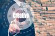 Businessman pressing a Creativity concept button on a circular d