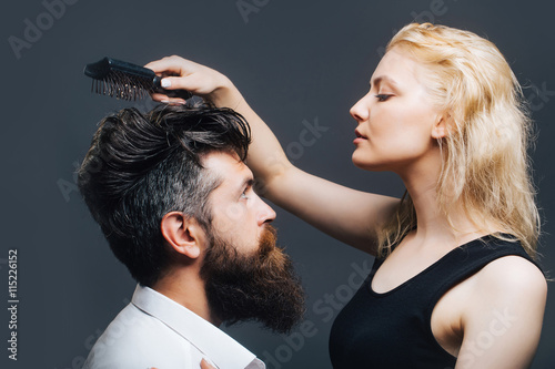 obraz lub plakat blonde hairdresser combing bearded man