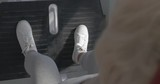 Senior woman working out on leg press machine in fitness centre. Focus on the feet pushing the platform