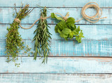Thyme, rosemary and mint hanging on twine over blue wood - 115235943