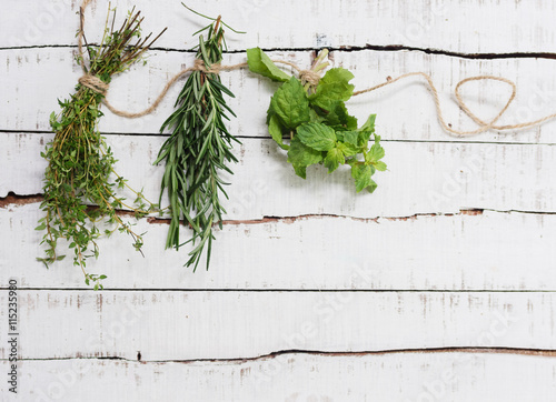 Thyme, rosemary and mint hanging on twine over white wood