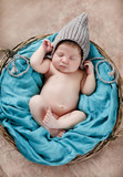 The nice newborn child, the brunette with short hair, in a gray knitted hat with long ties, sleeps peacefully in a round wattled basket on a soft blanket of turquoise color