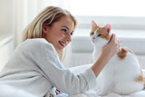 happy young woman with cat in bed at home