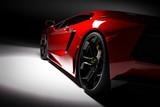 Red szybki samochód sportowy w reflektor, czarnym tle. Błyszczący, nowy, luksusowy.