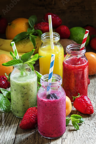 Fruit smoothies with colored straws in glass bottles, selective - 115251988