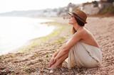Calm woman sitting alone on a sand beach