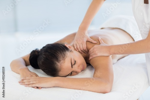 Relaxed naked woman receiving back massage Poster