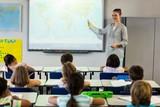Fototapety Teacher teaching schoolchildren using projector screen