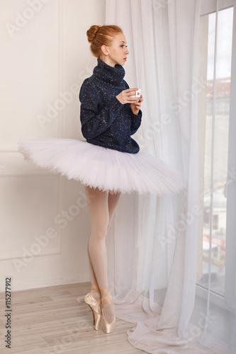 fototapeta na ścianę Ballerina drinking black tea near the window