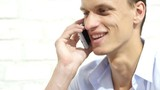 Close up of young smiling businessman talking on smartphone