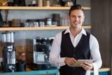 Waiter holding digital tablet in restaurant