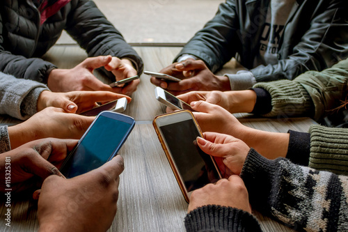 people using smart phones sitting at a table Poster