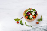Fresh salad in wooden bowl on white marble stone