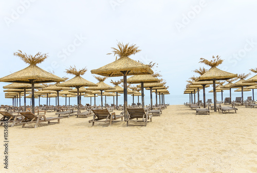 Thatched umbrellas and wooden lounge chairs on the beach.