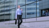 Happy young businessman walks down the stairs near modern office centre
