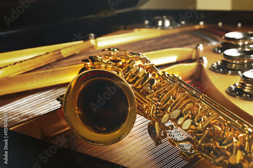 Staande foto Muziekwinkel Saxophone lying on the piano, close up