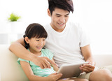 happy father and daughter  using tablet on sofa