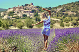 Blonde girl in a wide field of lavender. Young woman walking in purple lavender flowers. On the background of green trees and blue sky.
