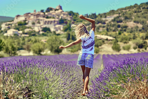 obraz PCV Blonde girl in a wide field of lavender. Young woman walking in purple lavender flowers. On the background of green trees and blue sky.