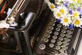field fresh flowers and black vintage typewriter