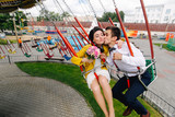 Stylish hipster newlyweds kissing while riding on high carousel in amusement park. Expressive wedding couple at carnival