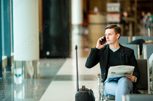 Urban business man talking on smart phone inside in airport. Casual young businessman wearing suit jacket. Handsome male model. Young man with cellphone at the airport while waiting for boarding.