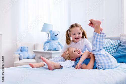 Kids playing in white bedroom © famveldman