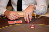 Closeup of hands of poker player with chips on poker table, sele - 115455398