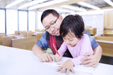 Young man teaches little girl to write