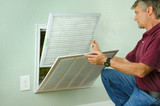 Professional repair service man or diy home owner a clean new air filter on a house air conditioner which is an important part of preventive maintenance. - 115481167