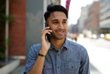 Fototapety Young Indian man in city talking on cell phone