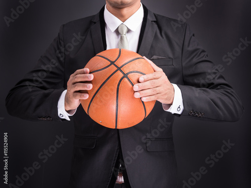 Poster Young businessman holding basketball ball