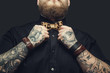 Bearded male with tattooes on his arms.