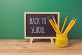 Back to school background with chalkboard and  pencils in emoji jar on wooden table