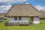 wiejski mały, biały domek pokryty strzechą z ogródkiem