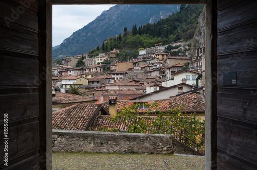 In de dag View on Limone through an open door, Lake Garda, Italy
